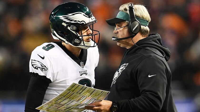 Eagles quarterback Nick Foles talks to coach Doug Pederson during the fourth quarter of an NFC wild-card game against the Bears last weekend.