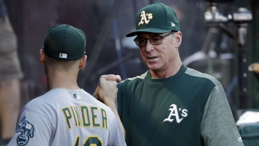 Oakland Athletics manager Bob Melvin, right, gives a fist-bump to Chad Pinder before the team's game against the Angels.