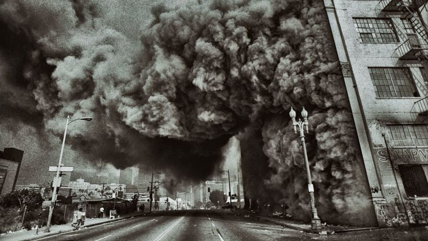 A building at 7th Street and Union Avenue in Los Angeles goes up in flames during the 1992 riots, the subject of a new exhibition at the California African American Museum.