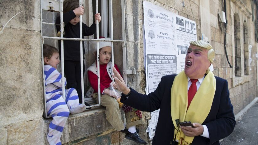 A man wears U.S. President Donald Trump's mask during the Purim festival in Mea Shearim ultra-Orthod