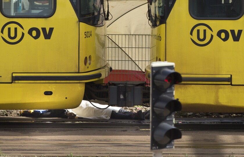 -FILE- In this Monday March 18, 2019, file image, the body of one of three victims is covered with a white sheet as it lies next to a tram after a shooting incident in Utrecht, Netherlands. The trial of a Dutch man of Turkish descent is starting Monday March 2, 2020, for allegedly opening fire on a tram in the central city of Utrecht last year, killing four people in what prosecutors say was a terror attack. (AP Photo/Peter Dejong, File)