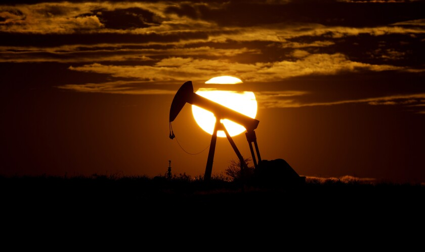 FILE - In this Wednesday, April 8, 2020, file photo, the sun sets behind an idle pump jack near Karnes City, USA. Oil prices pressed higher Monday, March 8, 2021, after strikes on major oil facilities in Saudi Arabia, the world's largest oil exporter, shook energy markets. (AP Photo/Eric Gay, File)