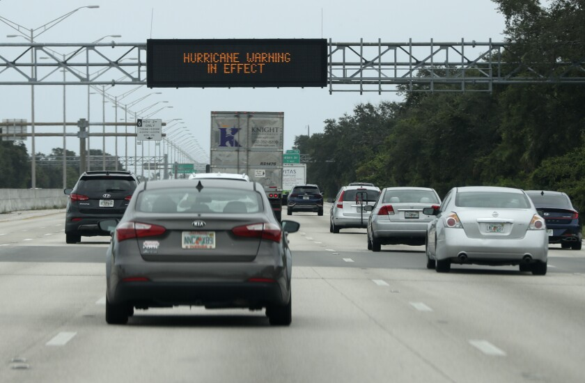Cars drive past a sign warning of weather on Interstate 95 near Boynton Beach, Fla., as the storm Isaias approaches.