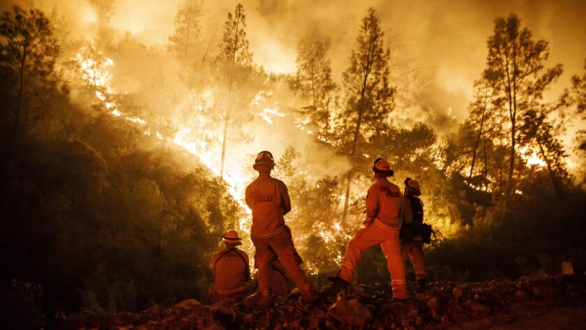 Firefighters monitor a burn operation on top of a ridge near the town of Ladoga, Calif., on Aug. 7.