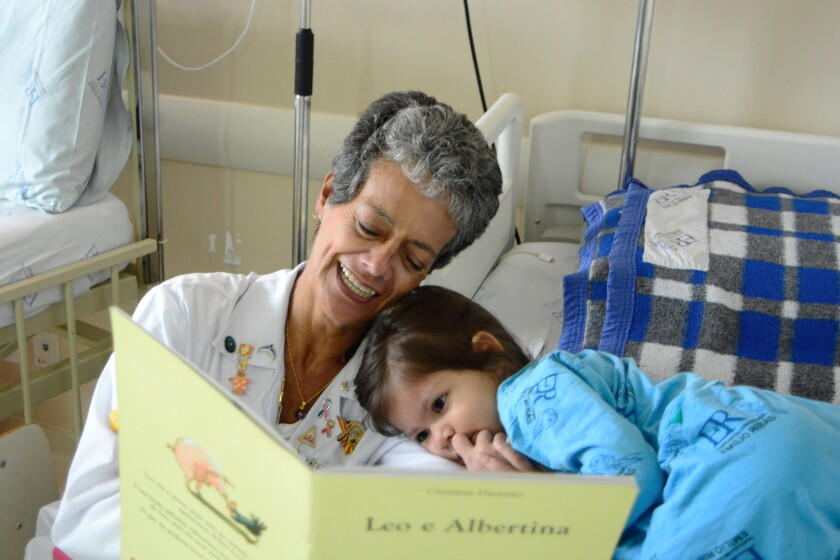 A storyteller reads to a young ICU patient.