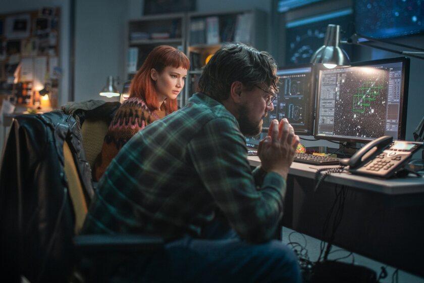 कार्यालय में एक महिला और एक पुरुष कंप्यूटर और एक लैंडलाइन टेलीफोन पर कुतरते हुए।