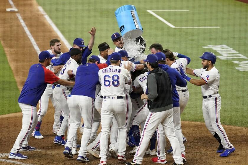Jonah Heim es rodeado por sus compañeros de los Rangers de Texas, quienes festejan luego que bateó un jonrón en la décima entrada del juego ante los Marineros de Seattle, el sábado 31 de julio de 2021 (AP Foto/Tony Gutiérrez)