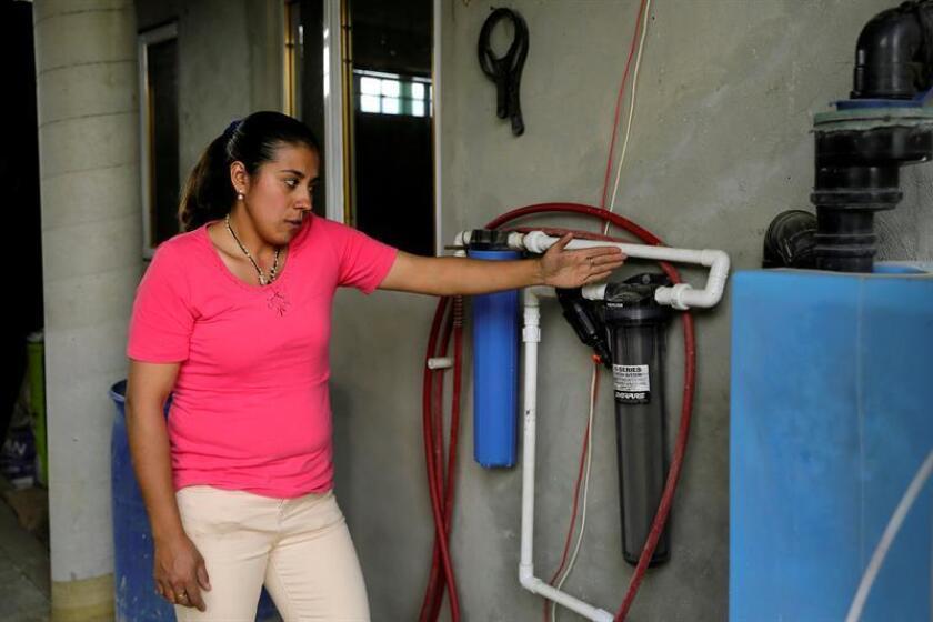 Fotografía del 17 de mayo de 2017 que muestra a la mexicana Adriana Bernal, habitante de la comunidad de Jardines de San Juan, en la delegación Tlalpan de la Ciudad de México, que muestra su sistema de captación de agua de lluvia promovido por la Fundación Isla Urbana. EFE