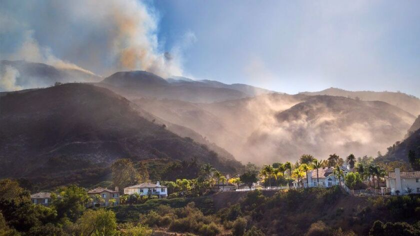 Firefighters declared the Canyon fire 95% contained Monday morning. The week-old fire, seen here burning above homes on the south side of the 91 Freeway, forced the evacuation of as many as 1,500 residents.