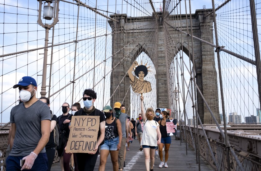 Protesters and activists walk across the Brooklyn Bridge June 6, 2020, in New York.