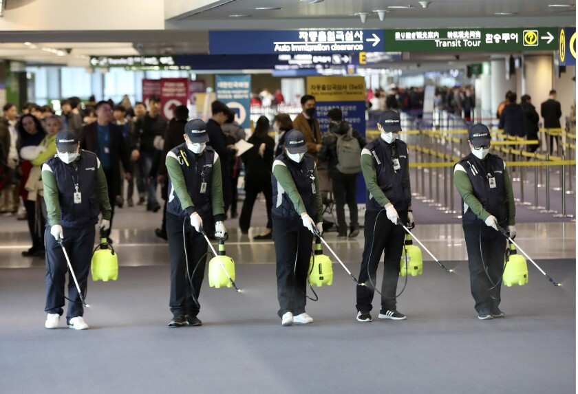 Workers spray antiseptic solution at Incheon International Airport in South Korea