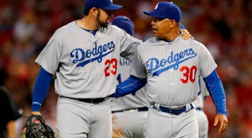 Adrián González (i) dialoga con el manager de los Dodgers, Dave Roberts, trasla derrota sufrida ante los Cincinnati Reds.