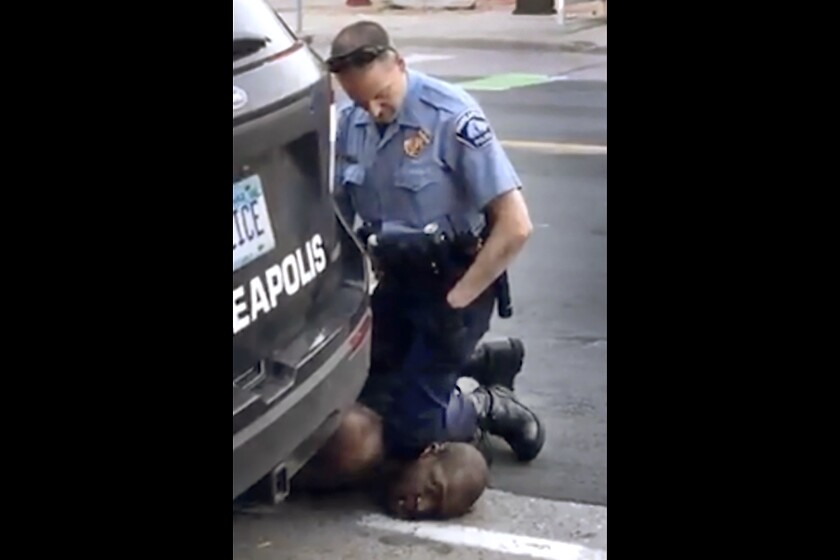 A Minneapolis officer kneels on the neck of a handcuffed man.