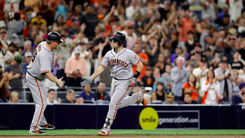 San Francisco Giants' Buster Posey is greeted by third base coach Phil Nevin after Posey's home run