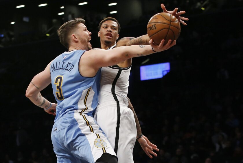 Brooklyn Nets forward Chris McCullough (1), blocks Denver Nuggets guard Mike Miller (3) as Miller goes up for a layup in the first half of an NBA basketball game, Monday, Feb. 8, 2016, in New York. (AP Photo/Kathy Willens)