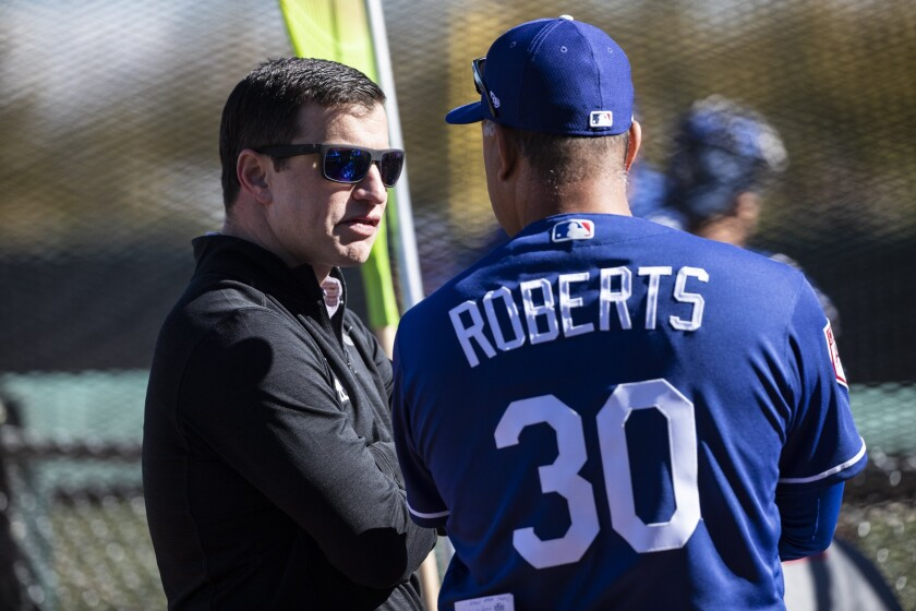 Dodgers President of Baseball Operations Andrew Friedman speaks with manager Dave Roberts.