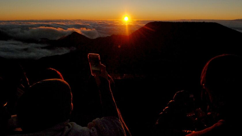 People watch as the sun rises in front of the summit of Haleakala volcano in Haleakala National Park on Hawaii's island of Maui on Jan. 22.