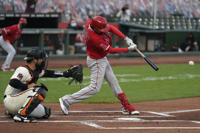 Angels third baseman Anthony Rendon hits a run-scoring single in front of Giants catcher Joey Bart.
