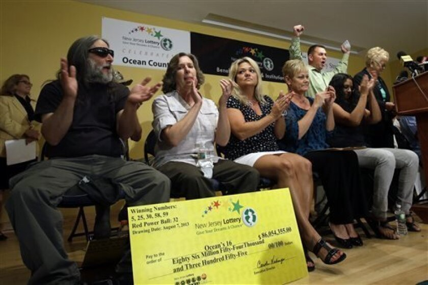 """Lottery winner Brian W. McCarthy raises his arms as other winners applaud Tuesday, Aug. 13, 2013, in Toms River, N.J. The """"Ocean's 16,"""" as a group of 16 public employees on the Jersey shore has been dubbed after snagging one of three winning tickets in last week's $448 million Powerball jackpot, gathered at an afternoon news conference in Toms River, where they work for the Vehicle Services department. The event comes one day after the nine women and seven men claimed their share of the jackpo"""