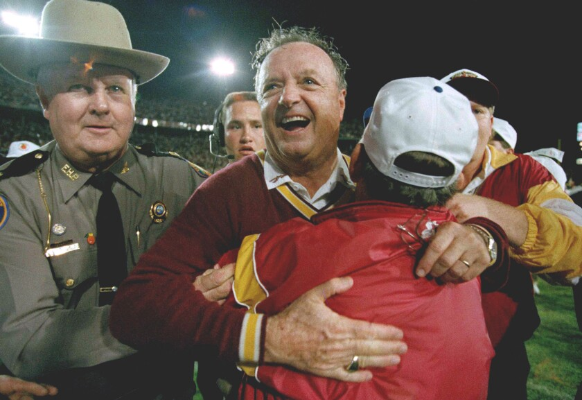 FILE - In this Jan. 1, 1994, file photo, Florida State University head football coach Bobby Bowden, center, receives a congratulatory hug after FSU defeated Nebraska 18-16 in the Orange Bowl in Miami. Bowden, the folksy Hall of Fame coach who built Florida State into an unprecedented college football dynasty, has died. He was 91. Bobby's son, Terry, confirmed to The Associated Press that his father died at home in Tallahassee, Fla., surrounded by family early Sunday, Aug. 8, 2021. (AP Photo/Doug Mills, File)
