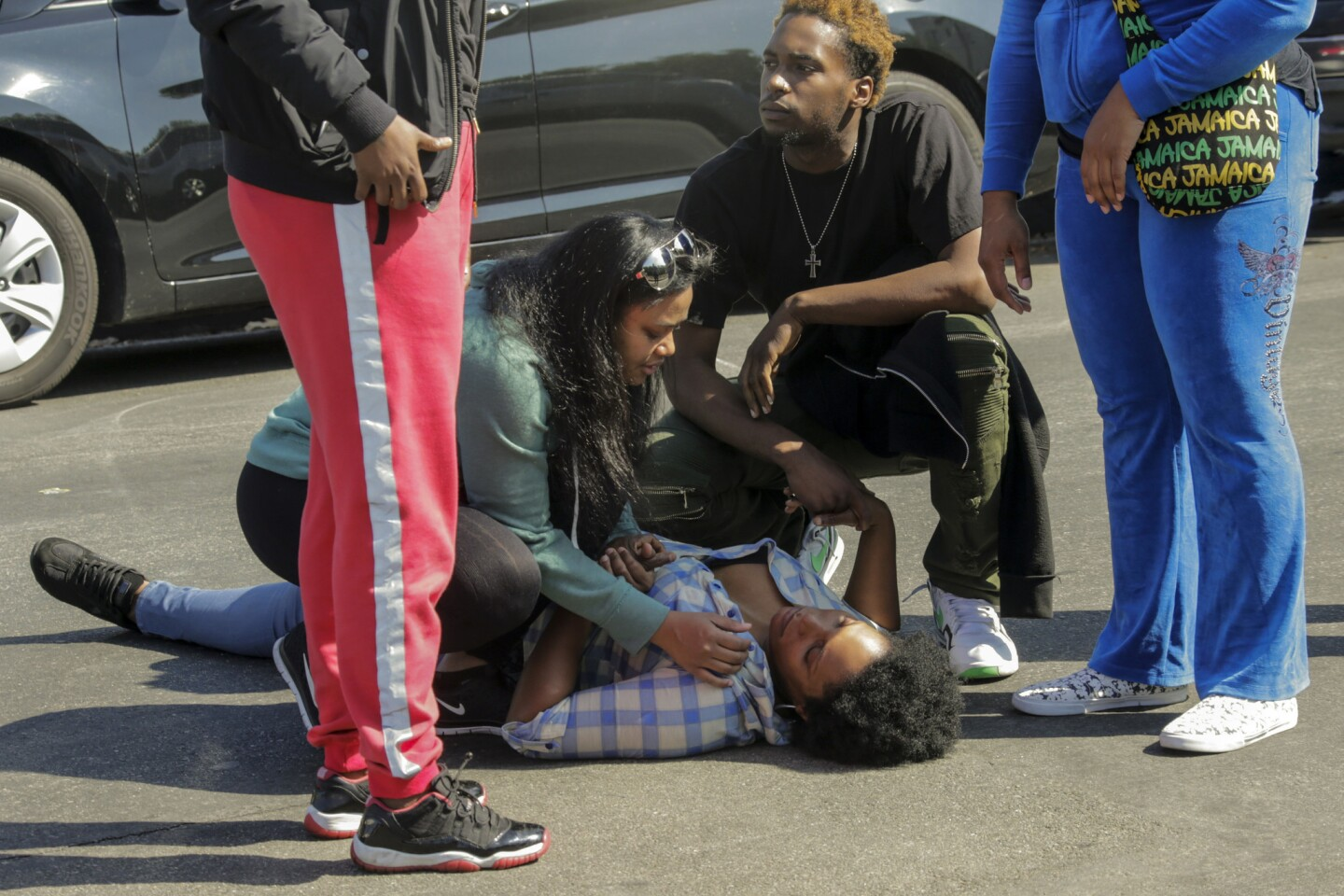 People tend to a woman who fainted after hearing of a friend's death in the West Adams shooting.