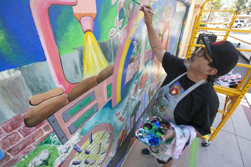 Muralist Mario Chacon worked on restoring a mural painted by fellow muralist Michael Schnorr in 1980 at the San Ysidro health clinic on Tuesday, Oct. 29, 2019. Schnorr passed away in 2012.