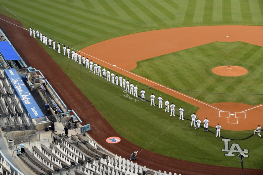 A general view as members of the Los Angeles Dodgers stand for the national anthem as Mookie Betts kneels.