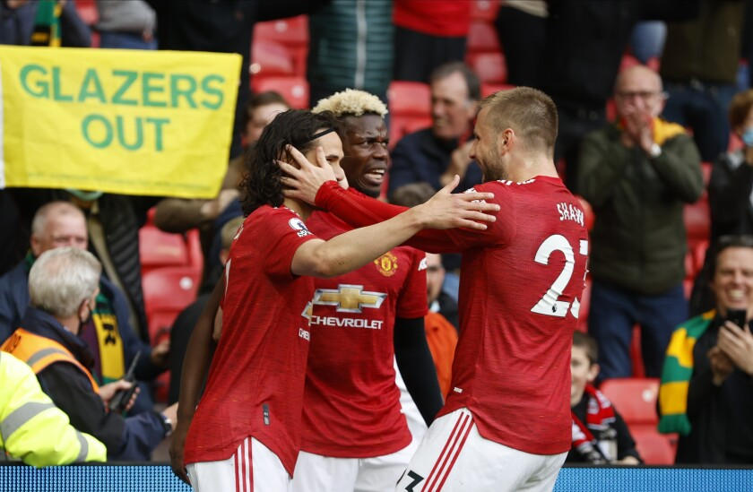 Manchester United's Edinson Cavani, left, celebrates scoring the opening goal with Manchester United's Paul Pogba, center, and Manchester United's Luke Shaw during the English Premier League soccer match between Manchester United and Fulham at Old Trafford stadium in Manchester, England, Tuesday, May 18, 2021. (AP Photo/Phil Noble, Pool)