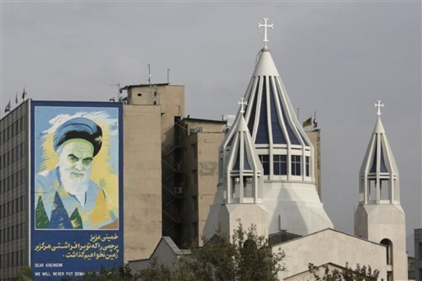 """In this Wednesday, Oct. 19, 2011 photo, a mural of the late Iranian revolutionary founder Ayatollah Khomeini is seen behind Saint Sarkis church, in Tehran, Iran. Since the Islamic Revolution 33 years ago, the walls and buildings of major cities have been an open air gallery to vilify the state's enemies and venerate the defenders of the theocracy. Government-sponsored murals became a centerpiece of the Islamic establishment's image-building machine: Depicting foes such as the U.S. with images including a skeleton for the Statue of Liberty, and celebrating the battle field dead from the 1980s war with Iraq as heroic martyrs guaranteed a place in heaven. The writing reads, """"dear Khomeini, we will never put down the flag that you have raised."""" (AP Photo/Vahid Salemi)"""