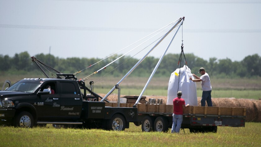 A crew hoists a bag holding the remains of a hot-air balloon that crashed Saturday near Lockhart, Texas.