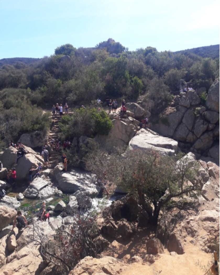A crowd of people at the Los Peñasquitos Canyon Preserve waterfall last year.