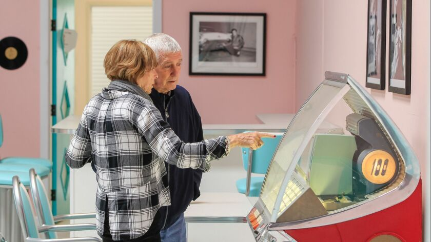 Bonita resident Sue Foley explains to her husband, Bill, how to operate the jukebox in the diner at Glenner Town Square, a mini memory village for Alzheimer's patients like Bill, that opens April 30 in Chula Vista.