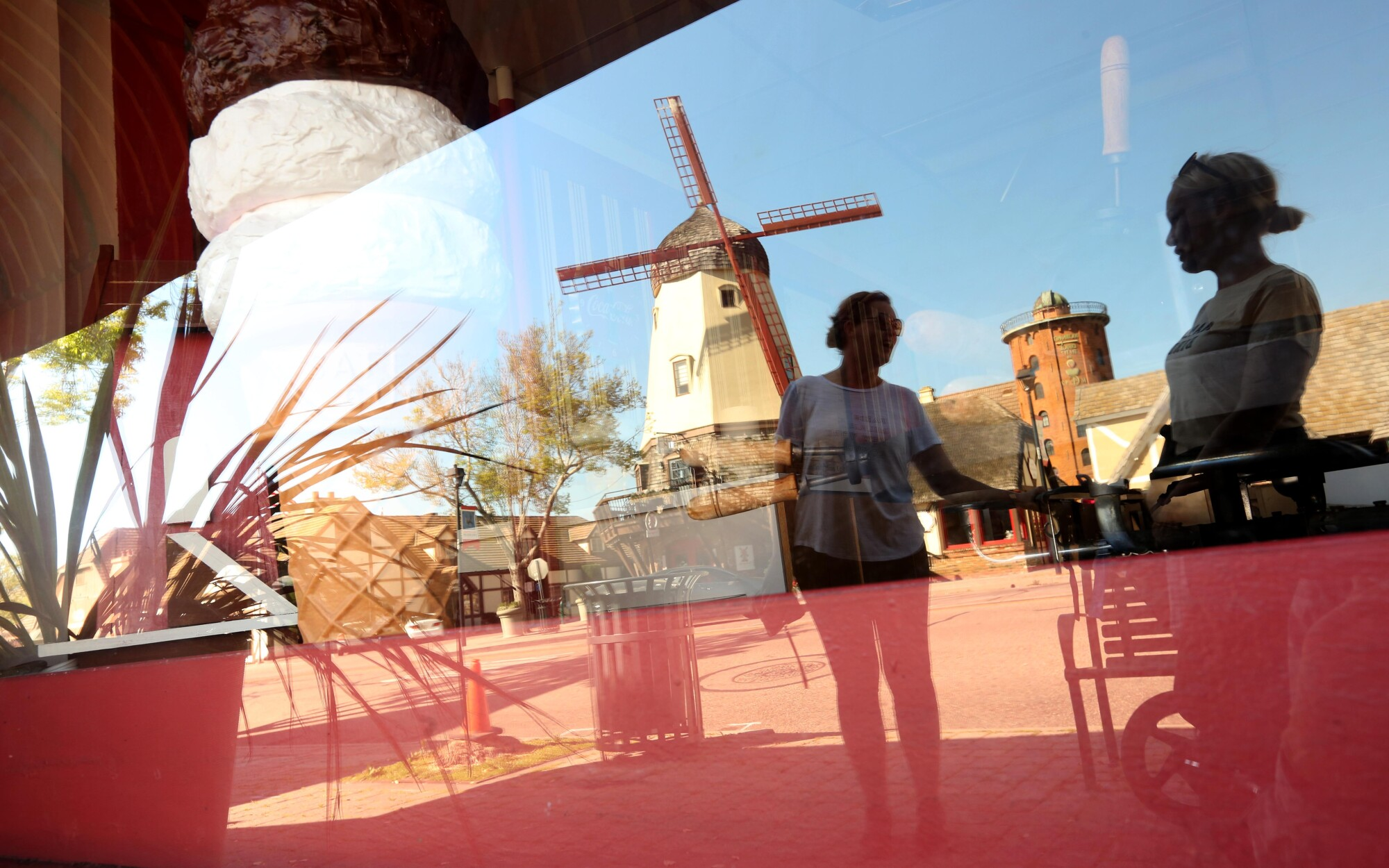 Alicja Clarke, right, and Jusyna Zimkowski talk while reflected in a storefront window along with a windmill on Alisal Road in Solvang, Calif., last week. Clarke has not been working since the Copenhagen House had to close due to the coronavirus pandemic.