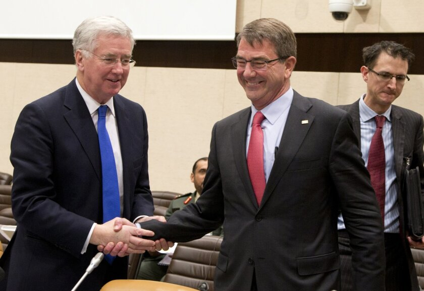 U.S. Secretary of Defense Ash Carter, second right, shakes hands with British Secretary of State for Defense Michael Fallon during a Counter-ISIL Coalition Ministerial meeting at NATO headquarters in Brussels on Thursday, Feb. 11, 2016. U.S. Defense Secretary Ash Carter expects Thursday's three-hou