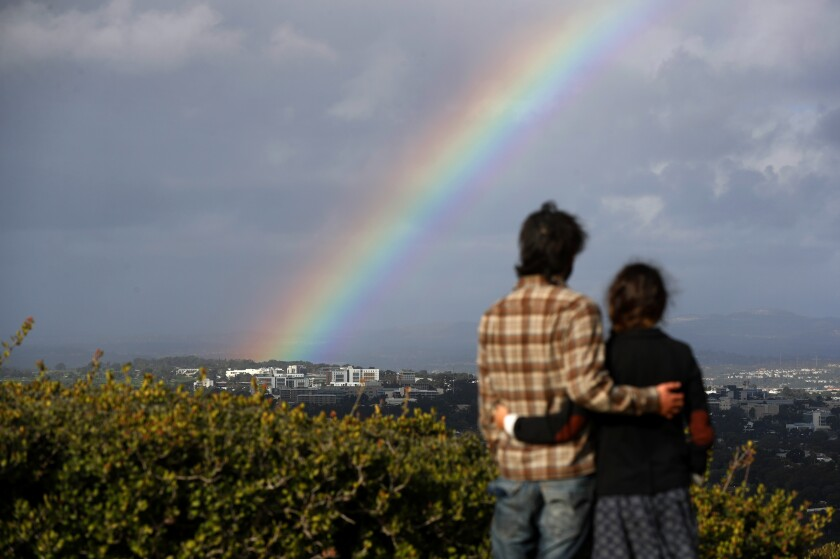 James Castaneda and Michel Vazquez look at a rainbow Monday as it forms north of UC San Diego during a winter storm.
