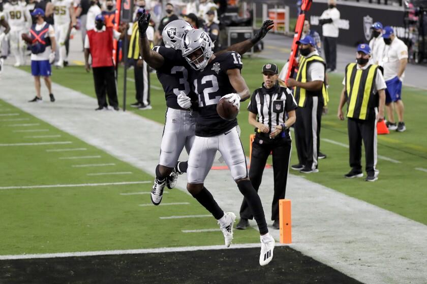 Las Vegas Raiders running back Jalen Richard, left, celebrates after wide receiver Zay Jones (12) scored a touchdown against the New Orleans Saints during the first half of an NFL football game, Monday, Sept. 21, 2020, in Las Vegas. (AP Photo/Isaac Brekken)