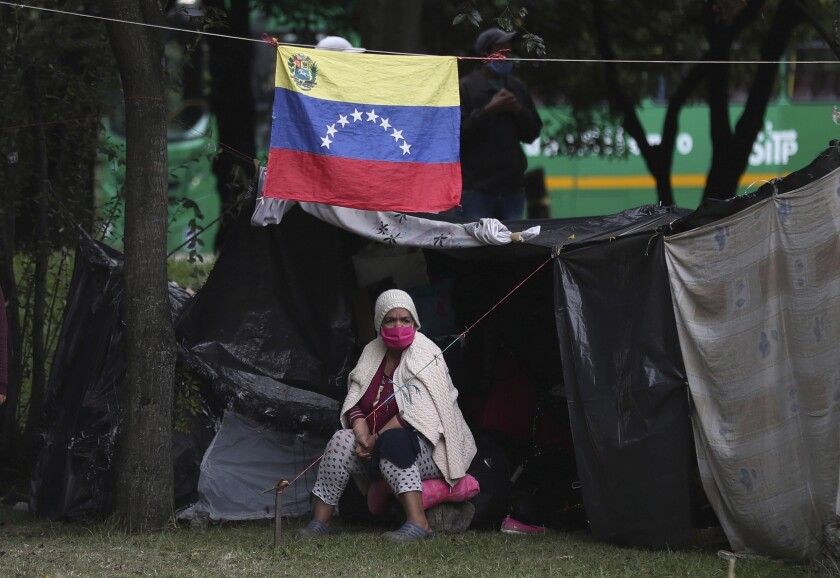 A homeless Venezuelan migrant wearing a face mask as protection amid the new coronavirus sits by her tent near the main bus terminal in Bogota, Colombia, Wednesday, June 3, 2020. Facing travel restrictions and no work due to the economic shut down to curb COVID-19, Venezuelan migrants here are waiting for help to get home. (AP Photo/Fernando Vergara)