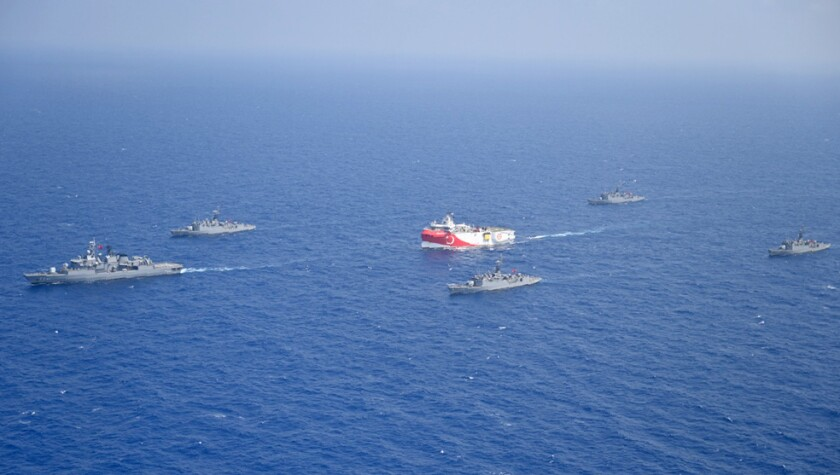 In this photo provided by the Turkish Defense Ministry, Turkey's research vessel, Oruc Reis, in red and white, is surrounded by Turkish navy vessels as it was heading in the west of Antalya on the Mediterranean, Turkey, Monday, Aug 10, 2020. Tension remains high between Greece and Turkey, whose warships are in the eastern Mediterranean where Turkey has sent a research vessel to carry out seismic research for energy resources in an area Greece says is on its continental shelf.(Turkish Defense Ministry via AP, Pool)