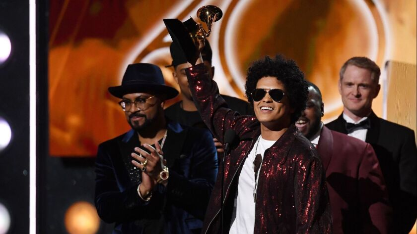 Bruno Mars hoists his Grammy for album of the year Sunday in New York.