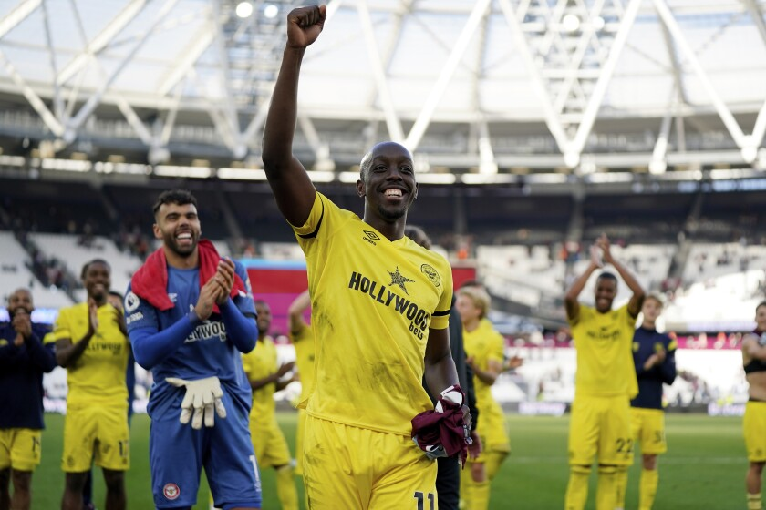 Brentford forward Yoane Wissa celebrates with supporters after winning an English Premier League soccer match against West Ham United at London Stadium in London, Sunday, Oct. 3, 2021. Brentford won 2-1. (AP Photo/Steve Luciano)