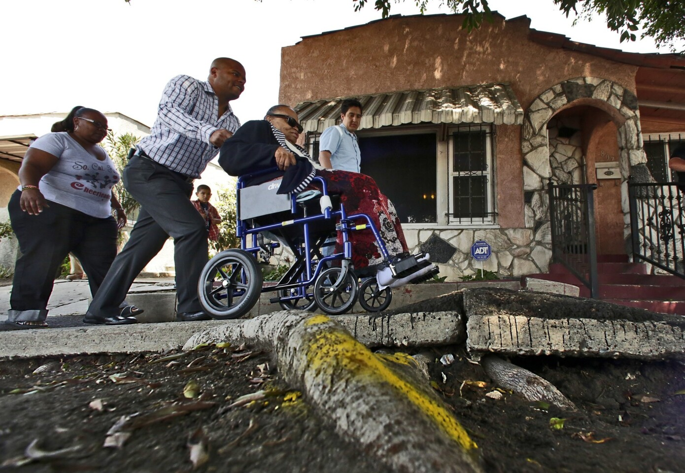 Bernard Parks Jr., chief of staff of Councilman Bernard Parks, pushes Helen Young, 80, in a wheelchair over a broken sidewalk in front her home on West Century Boulevard in Los Angeles, where Councilman Parks and the L.A. Neighborhood Initiative marked the start of several sidewalk repair projects.