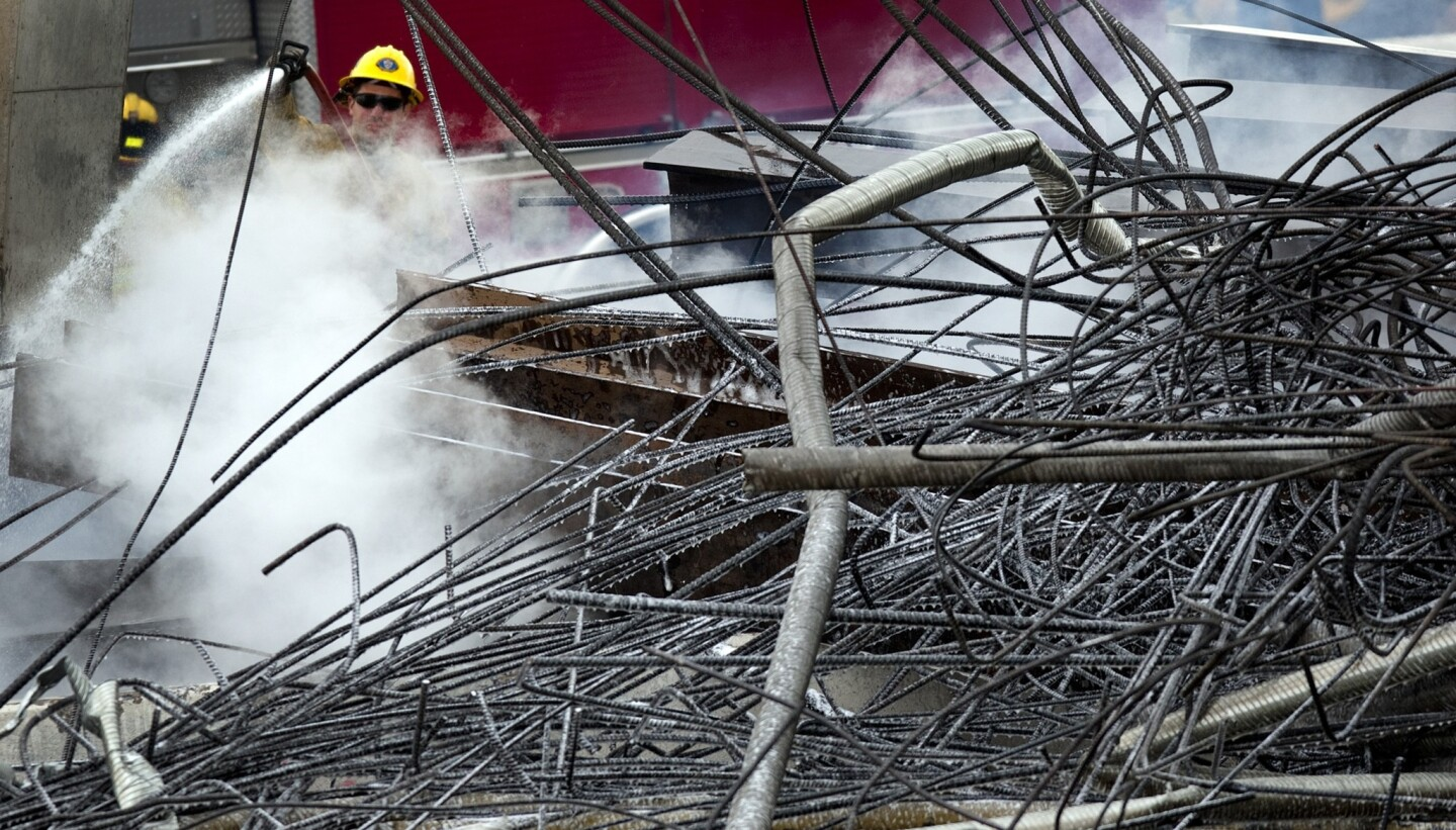 A San Bernardino County firefighter douses hot spots in the twisted metal and rebar remains of the Ranchero Road overpass on Interstate 15 in Hesperia.