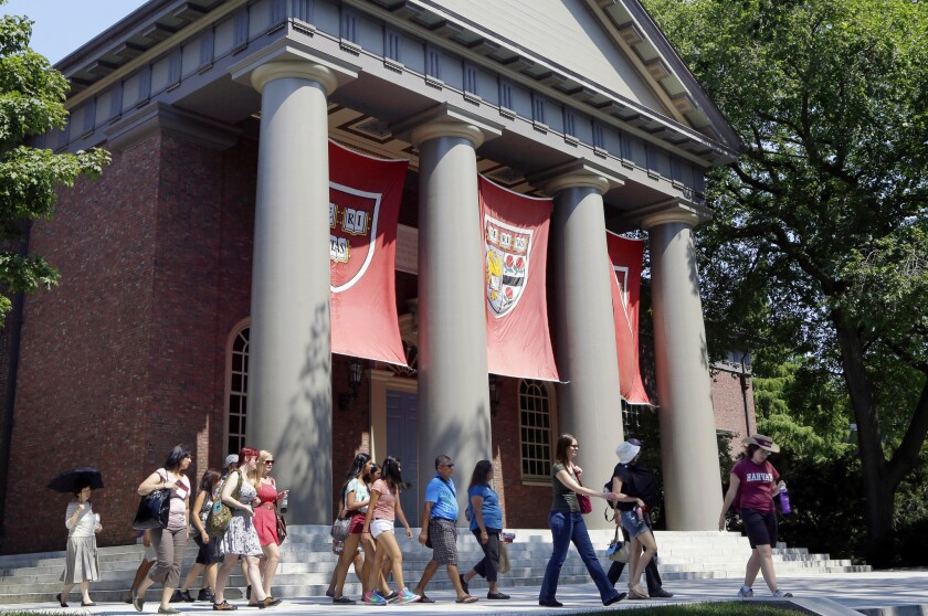A tour group walks through the campus of Harvard University in Cambridge, Mass., on Aug. 30, 2012.