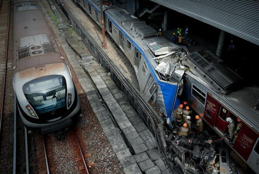 Firefighters work frantically to reach one of the drivers after two commuter trains collided in Rio in Janeiro on Wednesday, Feb. 27. EFE-EPA/Marcelo Sayao