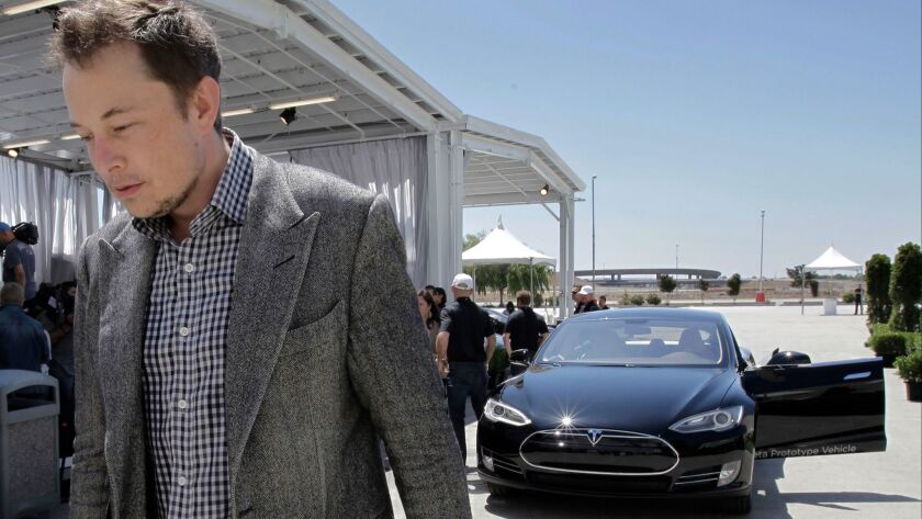 Tesla CEO Elon Musk walks past the Tesla Model S after a news conference at the Tesla factory in Fre