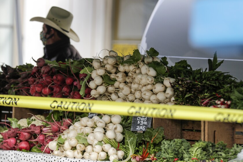 Farmers and their produce are separated by barricade tape at the Santa Monica Farmers Market.