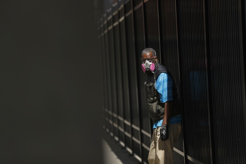 A man in Detroit wears a protective mask while waiting for a bus. Scientists would like to know more about which public health strategies are most effective at preventing the coronavirus from spreading.