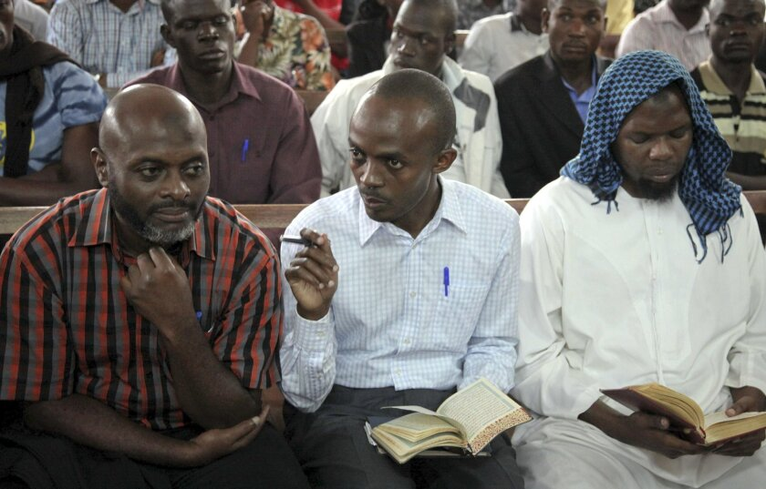 Muszafar Luyima, left, Issa Luyima, center, and Magundu Idris, right, are sentenced for their role in the 2010 bombings that killed 76 people who were watching the 2010 World Cup final, at the High Court in Kampala, Uganda Friday, May 27, 2016. A judge has given life sentences to five men convicted of carrying out the twin bombings in Kampala, while another convicted of being an accessory to terrorism was sentenced to a year of community service. (AP Photo/Stephen Wandera)