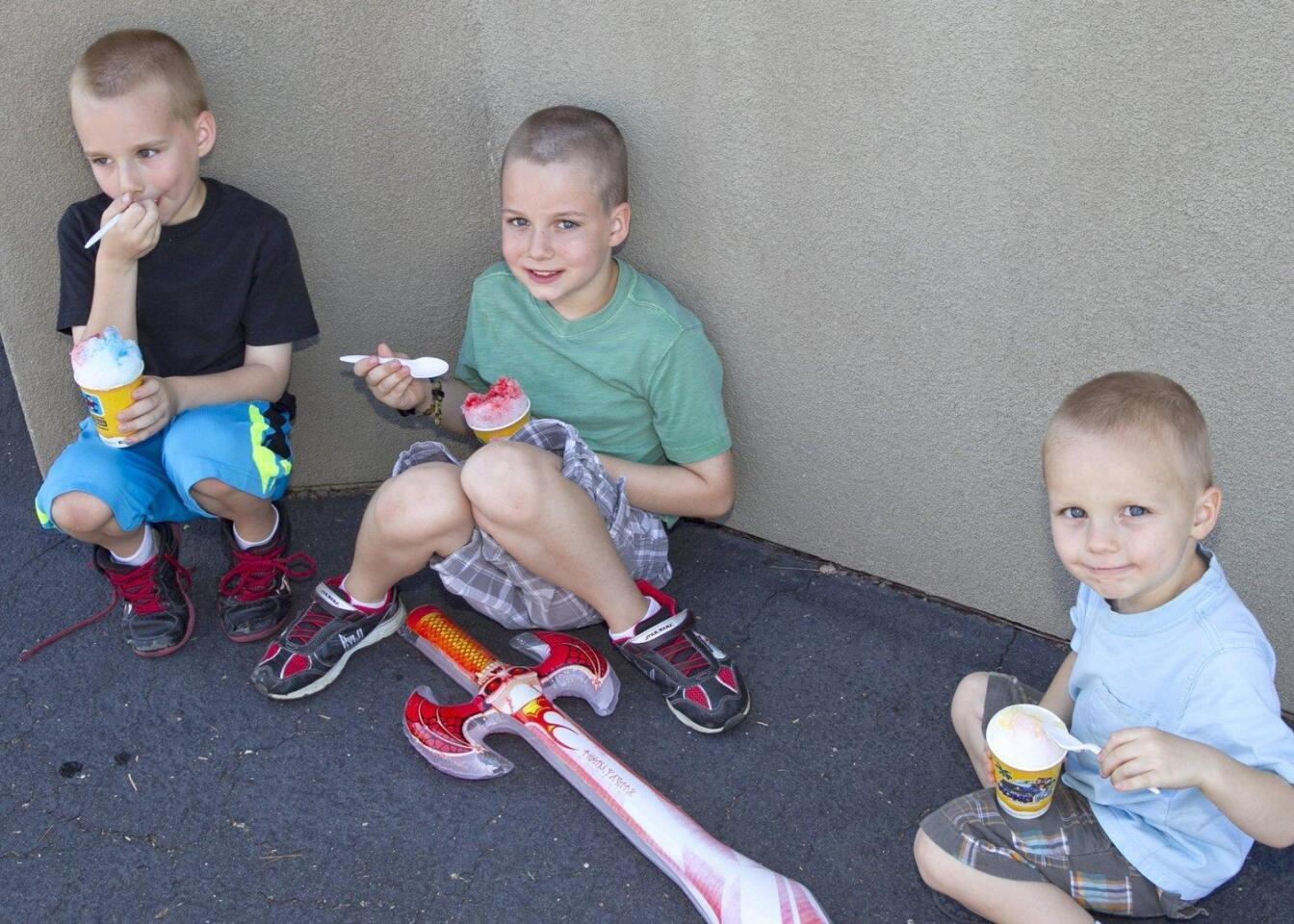 Brodie, Bennett, and Quinn Holt enjoy a cold snack in the shade