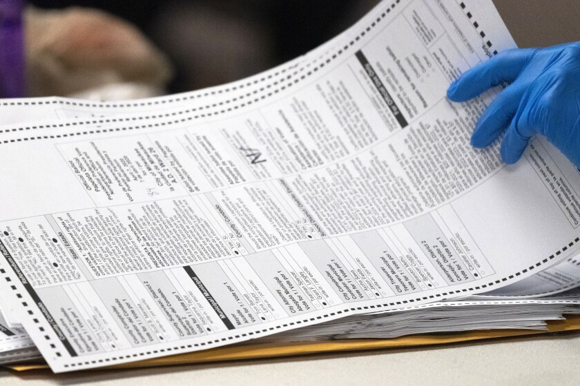 A Milwaukee Election Commission worker processes absentee ballots for the state's primary election in April.